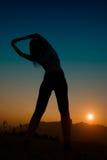 Fille de pratique de gymnaste au coucher du soleil vers le soleil images stock