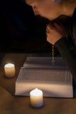 Fille de prière au-dessus de la bible avec une croix par lueur d'une bougie image stock