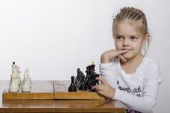 Fille de quatre ans avec un regard astucieux, échecs de jeux Photographie stock