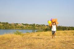 Fille de quatre ans courant avec des ballons Photographie stock libre de droits