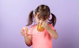 Fille de quatre ans dans un T-shirt rose manger le beignet et boire du jus image stock