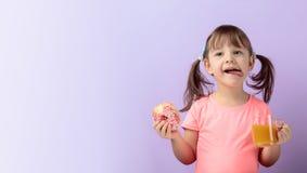 Fille de quatre ans dans un T-shirt rose manger le beignet et boire du jus photographie stock libre de droits