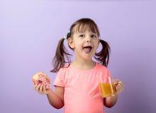 Fille de quatre ans dans un T-shirt rose manger le beignet et boire du jus photo libre de droits