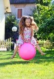 Fille de quatre ans mignonne rebondissant sur une grande bille Image libre de droits