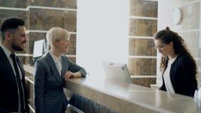 Fille de réceptionniste parlant avec les invités arrivés d'homme d'affaires et de femme d'affaires au sujet de l'enregistrement d banque de vidéos