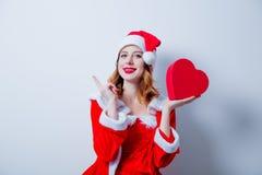 Fille de Santa Clous avec le cadeau de forme de coeur Photographie stock libre de droits