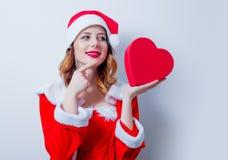 Fille de Santa Clous avec le cadeau de forme de coeur Images libres de droits