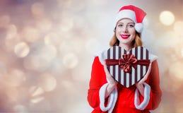 Fille de Santa Clous avec le cadeau de forme de coeur Images stock