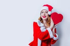 Fille de Santa Clous avec le cadeau de forme de coeur Image libre de droits
