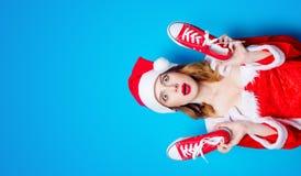 Fille de Santa Clous dans des vêtements rouges avec des chaussures en caoutchouc Photo libre de droits