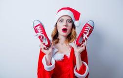Fille de Santa Clous dans des vêtements rouges avec des chaussures en caoutchouc Images stock