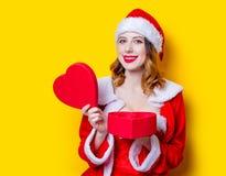 Fille de Santa Clous dans des vêtements rouges avec le boîte-cadeau Photographie stock