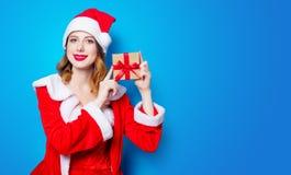 Fille de Santa Clous dans des vêtements rouges avec le boîte-cadeau Image stock