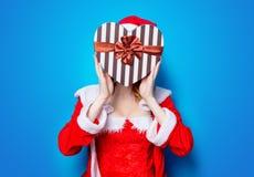 Fille de Santa Clous dans des vêtements rouges avec le boîte-cadeau Photos stock