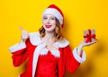 Fille de Santa Clous dans des vêtements rouges avec le boîte-cadeau Image libre de droits