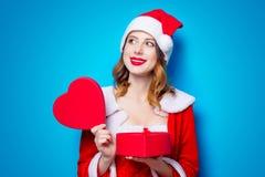 Fille de Santa Clous dans des vêtements rouges avec le boîte-cadeau Photo libre de droits