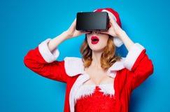 Fille de Santa Clous dans des vêtements rouges avec les verres 3D Photos stock