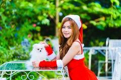 Fille de Santa d'Asiatique avec le chiot Photos stock