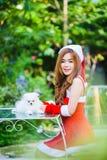 Fille de Santa d'Asiatique avec le chiot Photographie stock libre de droits