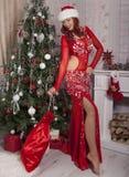 Fille de Santa de Noël avec le sac des cadeaux surprise Beau modèle de sourire de femme, longs cheveux bouclés Dame élégante en r Photo libre de droits