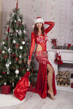 Fille de Santa de Noël avec le sac des cadeaux surprise Beau modèle de sourire de femme, longs cheveux bouclés Dame élégante en r Image libre de droits