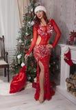 Fille de Santa de Noël avec le sac des cadeaux surprise Beau modèle de sourire de femme, longs cheveux bouclés Dame élégante en r Photo stock