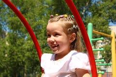 Fille de sept ans balançant sur une oscillation au terrain de jeu Photo libre de droits