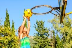 Fille de sept ans jouant le basket-ball photographie stock