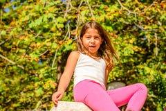 Fille de sept ans s'asseyant sur le mur photographie stock libre de droits