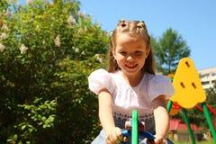 Fille de sept ans sur une oscillation au terrain de jeu Photographie stock libre de droits