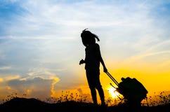Fille de silhouette avec une valise avec l'ensemble du soleil Images libres de droits