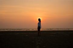 Fille de silhouette se tenant sur la plage et le coucher du soleil Photo libre de droits