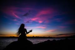 Fille de silhouette sur le coucher du soleil Images libres de droits