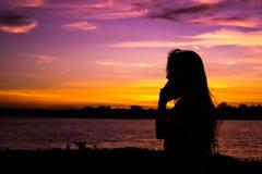 Fille de silhouette sur le coucher du soleil Photos stock