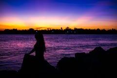 Fille de silhouette sur le crépuscule Photo libre de droits