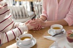 Fille de soin tenant des mains avec sa mamie Photographie stock libre de droits