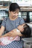 Fille de sommeil de transport de mère chinoise asiatique à l'intérieur d'un sta de MRT Image stock