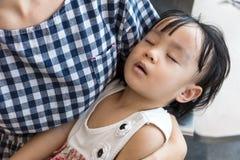 Fille de sommeil de transport de mère chinoise asiatique à l'intérieur d'un sta de MRT Images stock