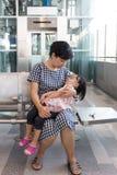 Fille de sommeil de transport de mère chinoise asiatique à l'intérieur d'un sta de MRT Photographie stock libre de droits