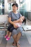 Fille de sommeil de transport de mère chinoise asiatique à l'intérieur d'un sta de MRT Image libre de droits