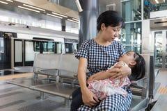 Fille de sommeil de transport de mère chinoise asiatique à l'intérieur d'un sta de MRT Images libres de droits