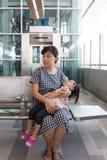 Fille de sommeil de transport de mère chinoise asiatique à l'intérieur d'un sta de MRT Photographie stock