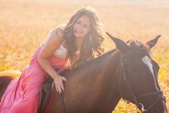 fille de sourire à cheval dans la robe photo libre de droits