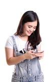 Fille de sourire à l'aide du smartphone d'isolement Photos stock