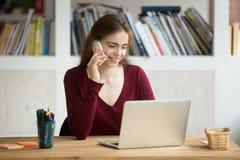 Fille de sourire à l'aide de l'ordinateur portable faisant l'appel de réponse se reposant au bureau images stock