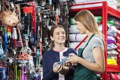 Fille de sourire achetant le magasin de Toy From Saleswoman In Pet images libres de droits
