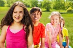 Fille de sourire avec de longs cheveux et ses amis Photographie stock libre de droits