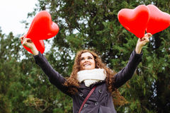 Fille de sourire avec des ballons sous forme de coeur Photo stock