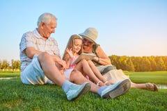 Fille de sourire avec des grands-parents, comprimé Photographie stock
