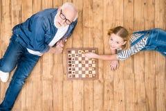 Fille de sourire avec l'homme supérieur jouant des échecs sur le plancher en bois images stock